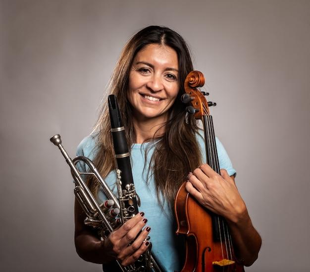 Kobieta trzyma instrumenty muzyczne na szarość