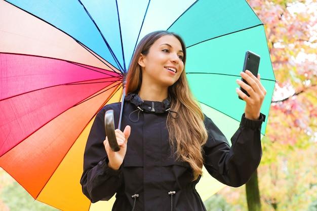 Kobieta trzyma inteligentny telefon pod tęczowym parasolem jesienią na zewnątrz