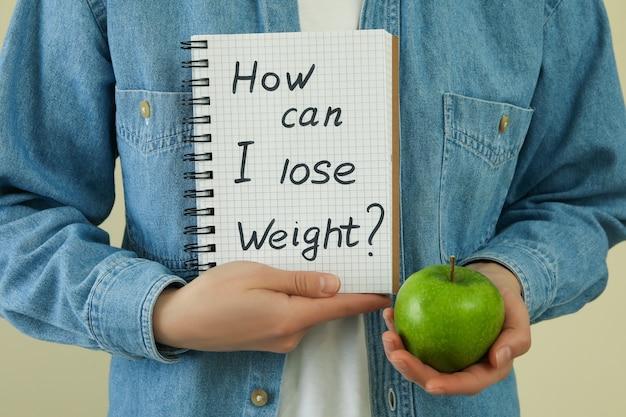Kobieta trzyma jabłko i tekst jak mogę schudnąć?