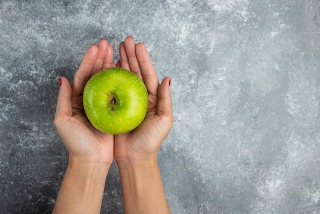 Kobieta trzyma jabłko obiema rękami na marmurze.