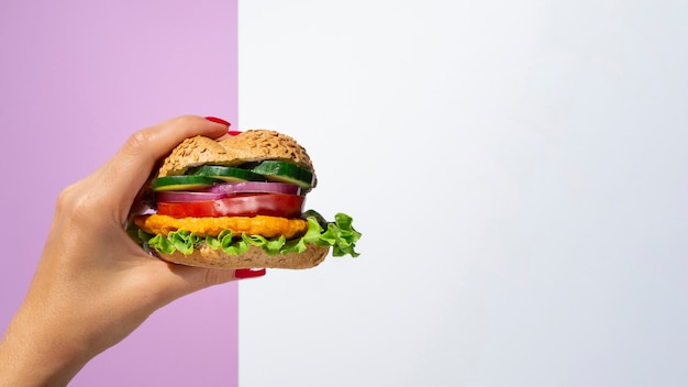 Kobieta trzyma jarzynowego hamburger w jej ręce