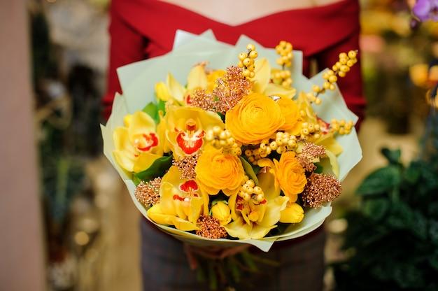Kobieta trzyma jasny żółty bukiet kwiatów na walentynki