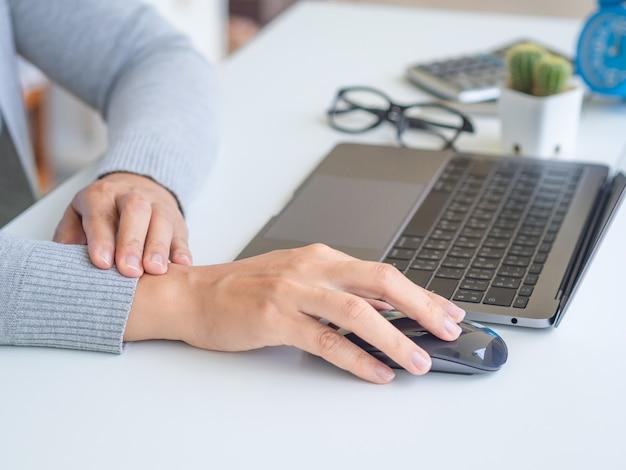 Kobieta trzyma jej ból nadgarstka od długiego korzystania z komputera.