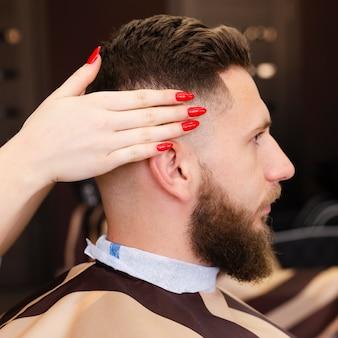 Kobieta trzyma jej klienta głowy widok z boku
