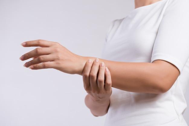 Kobieta trzyma jej kontuzji ręki nadgarstek, uczucie bólu. opieka zdrowotna i koncept medyczny.