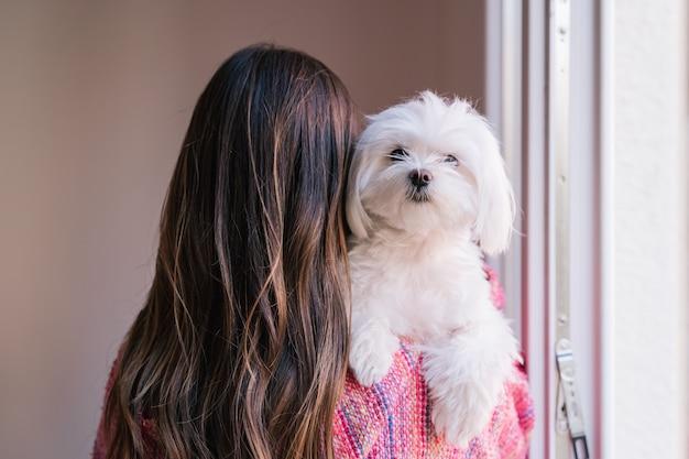 Kobieta trzyma jej maltańskiego psa na ramieniu w domu