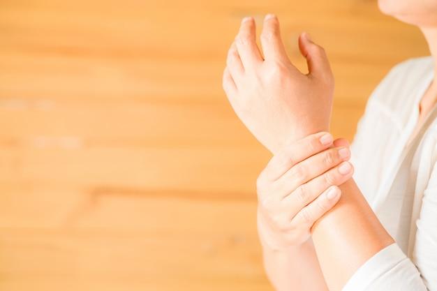 Kobieta trzyma jej nadgarstek symptomatyczny zespół biurowy