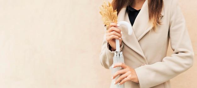 Kobieta trzyma jesienny liść z miejsca na kopię