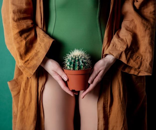 Kobieta trzyma kaktusa w jej ręce na poziomie stóp