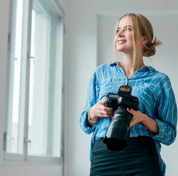 Kobieta trzyma kamerę i patrzeje przez okno