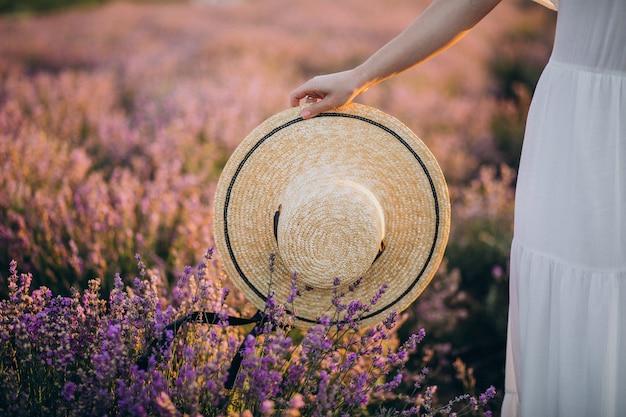 Kobieta trzyma kapelusz w polu lawendy z bliska