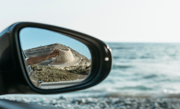 Kobieta trzyma kapelusz z okna w widoku lusterka samochodowego