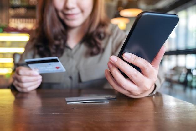 Kobieta trzyma kartę kredytową i korzystając z bankowości mobilnej siedząc w kawiarni