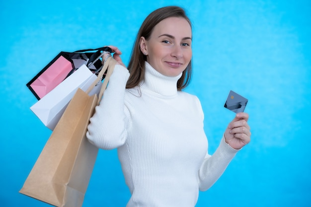 Kobieta trzyma kartę kredytową i torby na zakupy na niebieskiej ścianie.