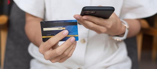 Kobieta trzyma kartę kredytową i używa smartfona z ekranem dotykowym do zakupów online podczas składania zamówień w kawiarni lub biurze. koncepcja biznesowa, technologia, e-commerce i płatności online