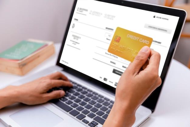 Kobieta trzyma kartę kredytową i za pomocą laptopa. kobiety pracujące w domu. zakupy online, handel elektroniczny, bankowość internetowa, wydawanie pieniędzy, praca z domu. koncepcja zakupów online technologii