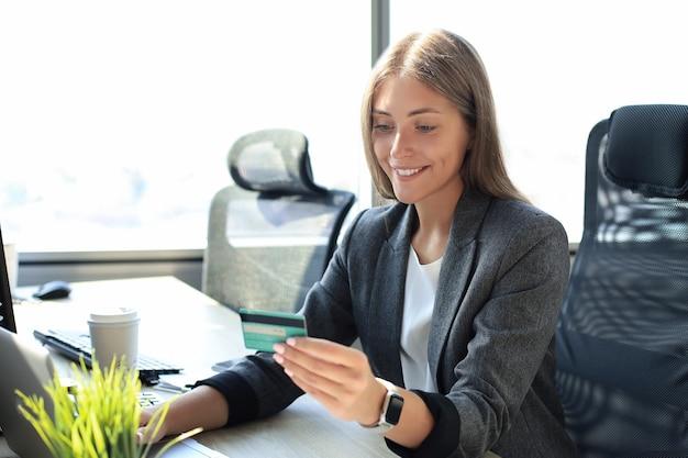 Kobieta trzyma kartę kredytową na laptopie dla koncepcji zakupy online.