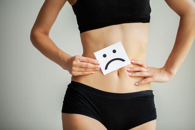 Kobieta trzyma kartę ze smutnym uśmiechem w pobliżu brzucha