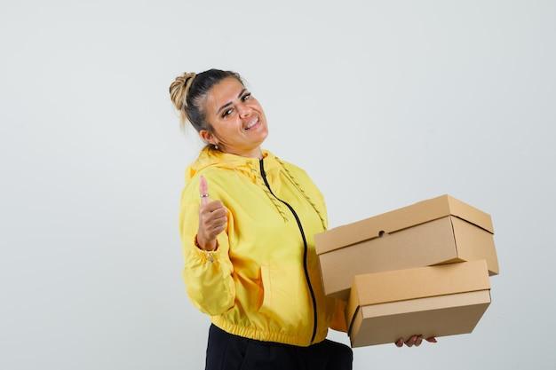 Kobieta trzyma kartony, pokazując kciuk w sportowym garniturze i wyglądająca na pewną siebie. przedni widok.