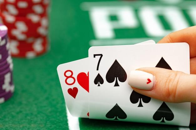 Kobieta trzyma karty do gry gra w pokera przy zielonym stole