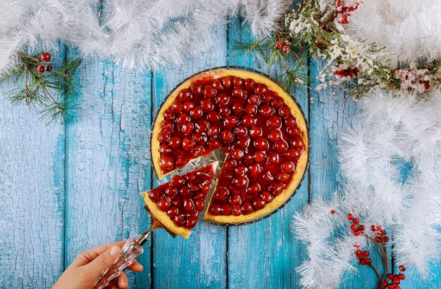 Kobieta trzyma kawałek ciasta wiśniowego na niebieskim drewnianym stole z dekoracją świąteczną.