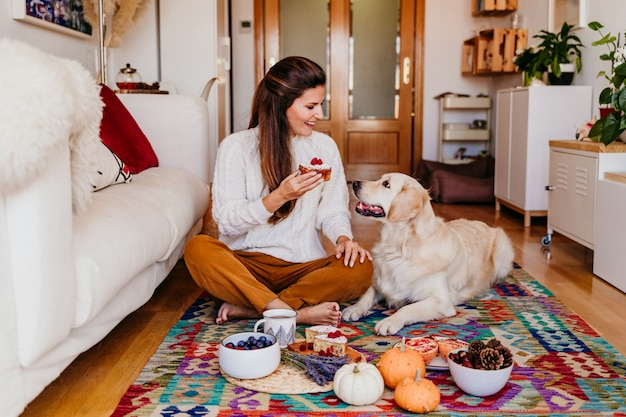 Kobieta trzyma kawałek cukierki w domu podczas śniadania.
