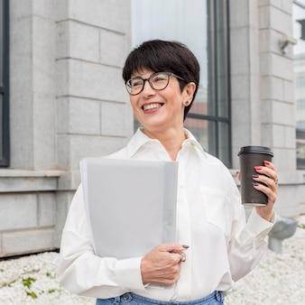 Kobieta trzyma kawę i uśmiecha się