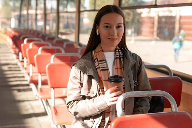 Kobieta trzyma kawę w publicznym transporcie tramwajowym