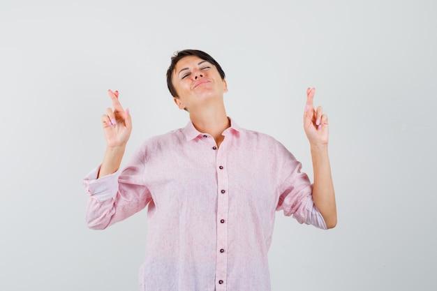 Kobieta trzyma kciuki w różowej koszuli i wygląda spokojnie. przedni widok.