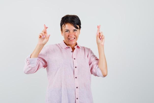 Kobieta trzyma kciuki w różowej koszuli i wygląda wesoło. przedni widok.