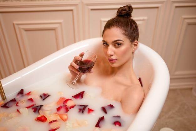 Kobieta trzyma kieliszek czerwonego wina w kąpieli