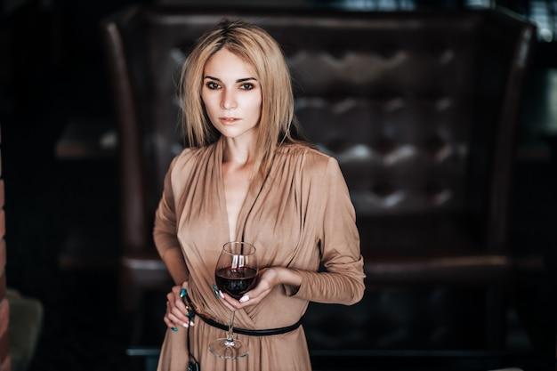 Kobieta trzyma kieliszek czerwonego wina w restauracji