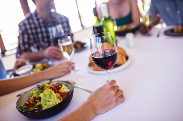 Kobieta trzyma kieliszek do wina w restauracji