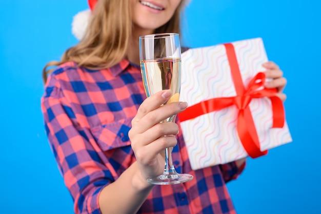 Kobieta trzyma kieliszek szampana i obecne pudełko