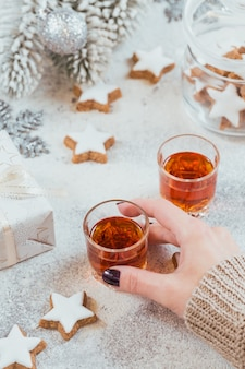 Kobieta trzyma kieliszek whisky, brandy lub likieru. ciasteczka, napoje i dekoracje zimowe wakacje na białym tle. koncepcja świąt sezonowych.