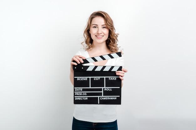 Kobieta trzyma kino klapy produkcji produkcji patrząc