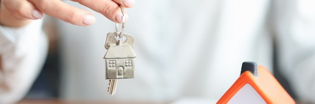 Kobieta trzyma klucz w dłoniach w pobliżu zabawkowego domu zbliżenia