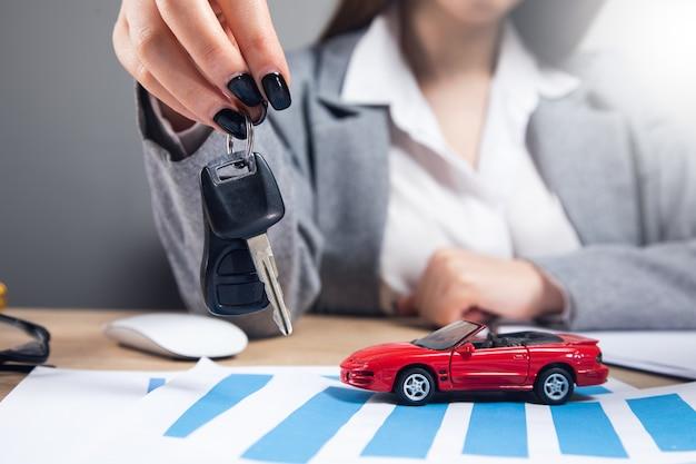 Kobieta trzyma klucz z modelem samochodu na wykresie