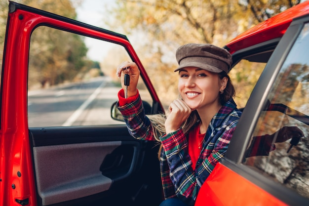 Kobieta trzyma klucze nowego samochodu. szczęśliwy nabywca kupił czerwony samochód. kierowca patrzeje kamery obsiadanie w samochodzie