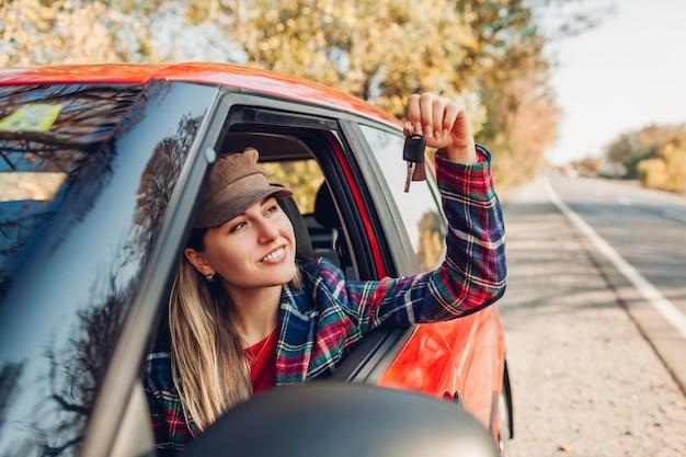 Kobieta trzyma klucze nowego samochodu. szczęśliwy nabywca kupił czerwony samochód. kierowca patrzeje klucze siedzi w samochodzie