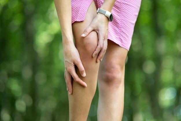 Kobieta trzyma kolano rękami o silnym bólu.