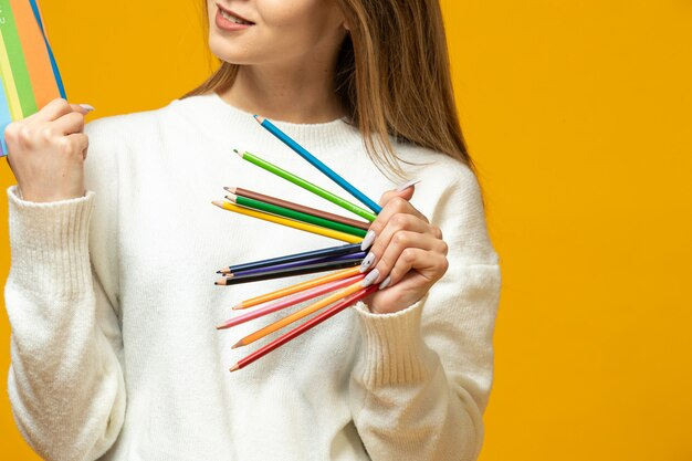Kobieta trzyma kolorowe ołówki i kolorowy notatnik