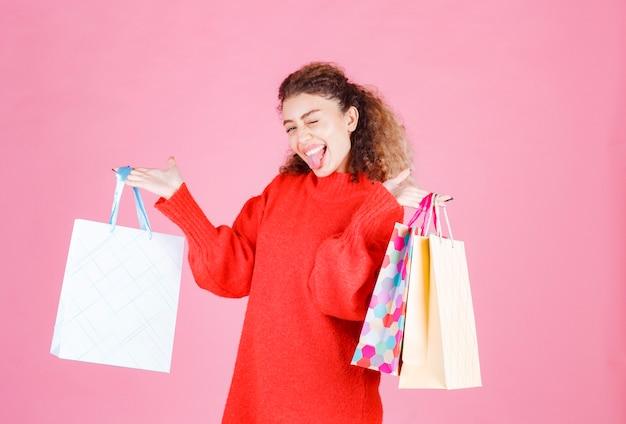 Kobieta trzyma kolorowe torby na zakupy i uczucie szczęścia.