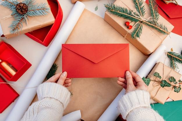 Kobieta trzyma kopertę podczas gdy pakujący prezenty dla bożych narodzeń na stole