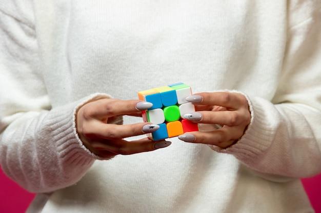 Kobieta trzyma kostkę rubika w ręce