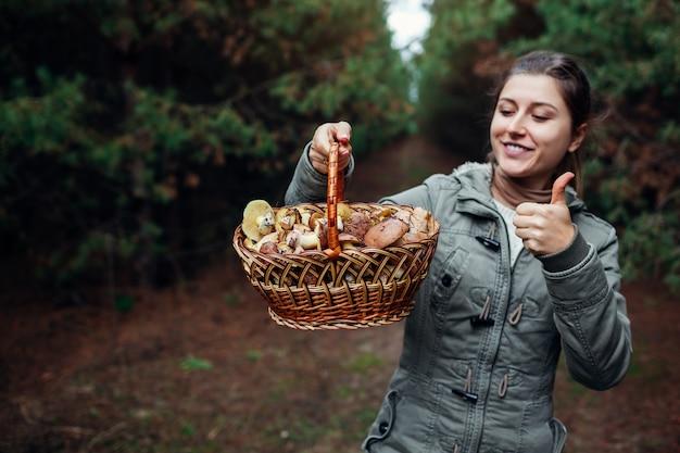 Kobieta trzyma kosz grzybów oleistych w lesie jesienią. zbieranie świeżych organicznych grzybów slippery jack