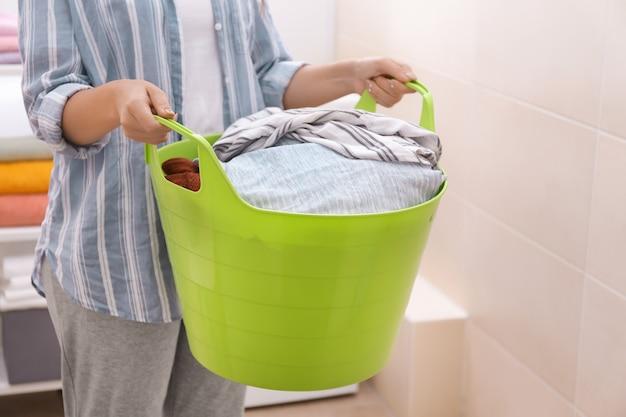 Kobieta trzyma kosz na pranie z brudnymi ubraniami w łazience