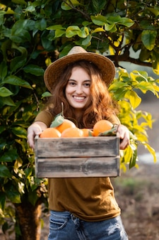 Kobieta trzyma kosz z pomarańczami