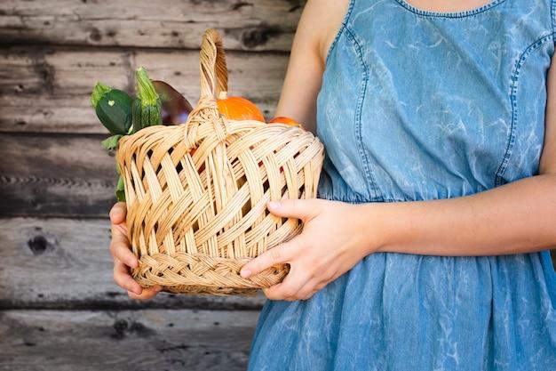 Kobieta trzyma kosz z warzywami blisko do jej klatki piersiowej