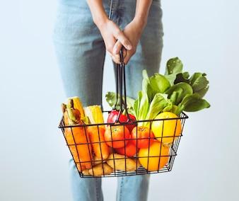 Kobieta trzyma koszyk warzywny